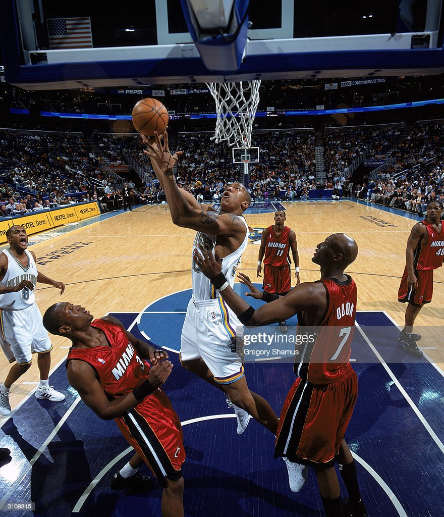 David West of the New Orleans Hornets goes up for a shot between Dwyane Wade and Lamar Odom of the Miami Heat during the game at New Orleans Arena on...