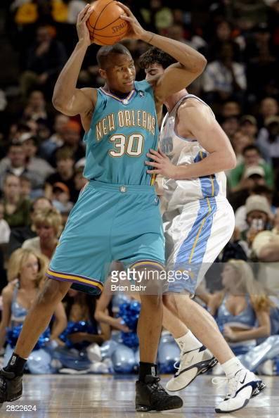 David West of the New Orleans Hornets posts up Nikoloz Tskitishvili of the Denver Nuggets on December 16 2003 at the Pepsi Center in Denver Colorado...