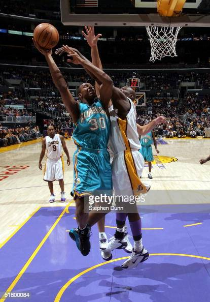 David West of the New Orleans Hornets takes a shot guarded by Lamar Odom of the Los Angeles Lakers on November 28 2004 at Staples Center in Los...
