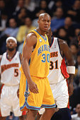 David West of the New Orleans/Oklahoma City Hornets frowns as he walks on the court during a game against the Golden State Warriors at The Arena in...