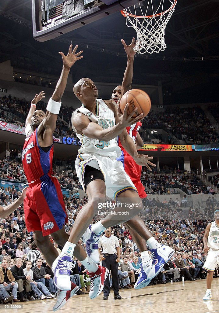 David West of the New Orleans/Oklahoma City Hornets shoots a reverse layup against Cuttino Mobely and Quinton Ross of the Los Angeles Clippers on...