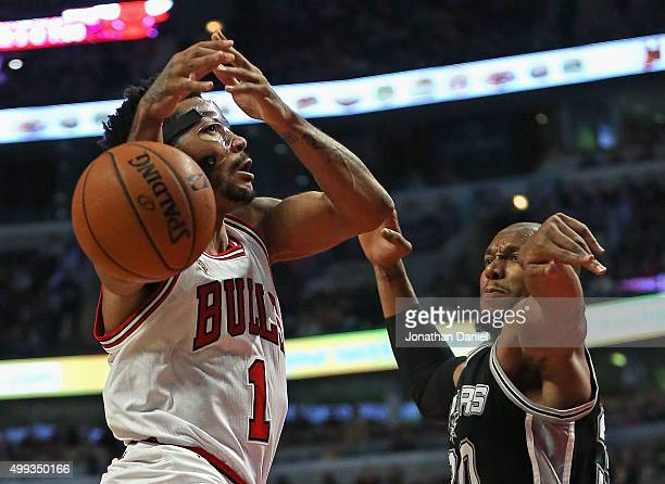 David West of the San Antonio Spurs knocks the ball away from Derrick Rose of the Chicago Bulls at the United Center on November 30 2015 in Chicago...