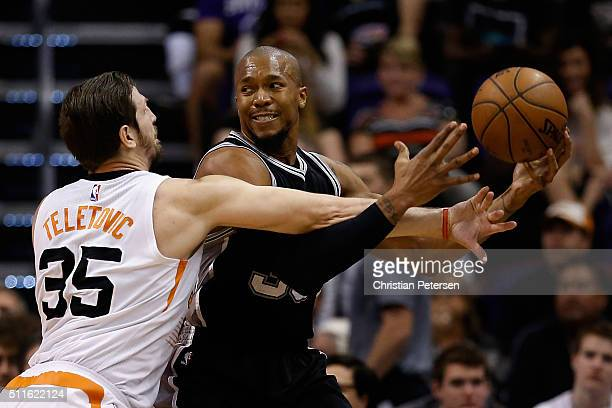 David West of the San Antonio Spurs looks to pass under pressure from Mirza Teletovic of the Phoenix Suns during the first half of the NBA game at...