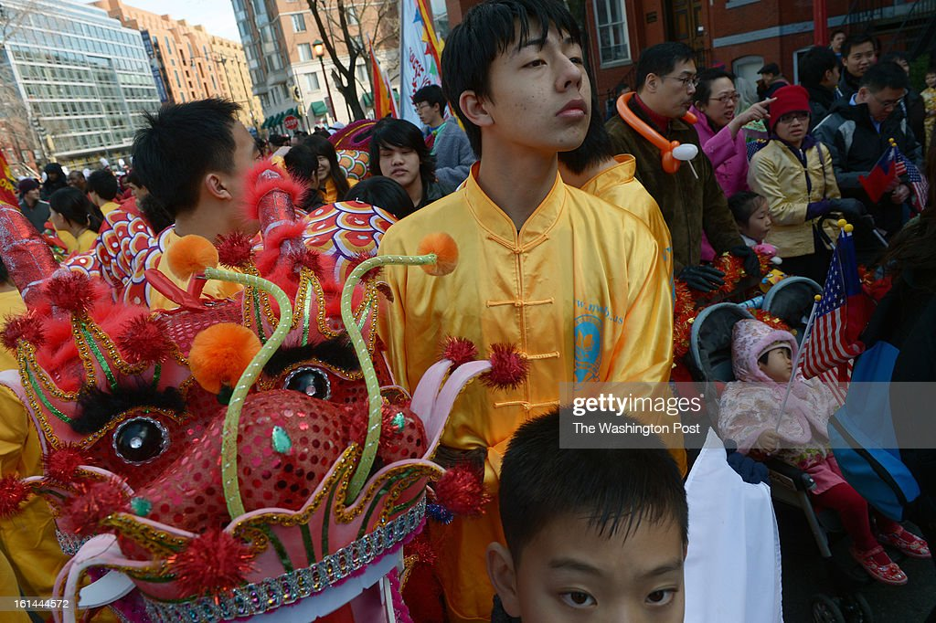David White, top right, and Kevin Liang, bottom, of the New World Bilingual Institute Dragon Dance Team wait for the start of a parade to celebrate the Chinese New Year on Sunday February 10, 2013 in Washington, DC. Scores of people turned out for the event that ushers in the year of the Snake.