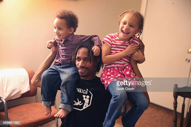 David Whitt plays with his children David Jr and Aurolla while preparing Thanksgiving dinner with his wife at their home in the Canfield Green...
