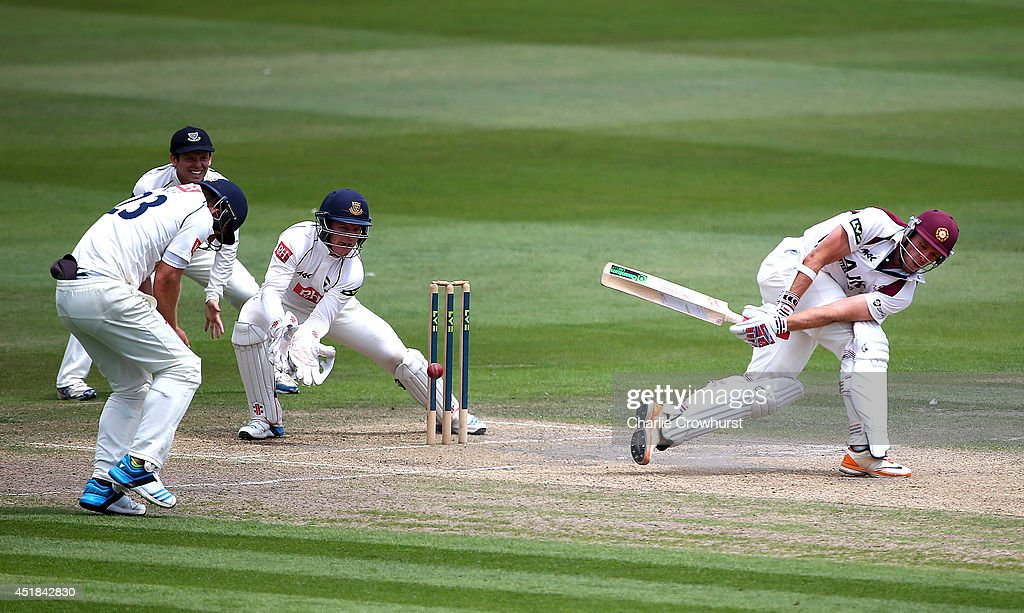 David Willey of Northamptonshire hits out while Ben Brown of Sussex looks on during day three of the LV County Championship match between Sussex and...