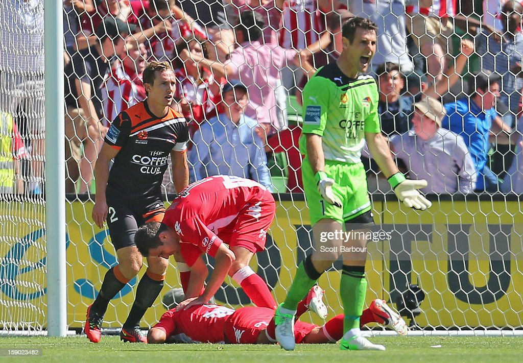 David Williams of the Heart falls to the ground after colliding with goalkeeper Michael Theo (R) of the Roar as he scores the Hearts first goal during the round 15 A-League match between the Melbourne Heart and the Brisbane Roar at AAMI Park on January 6, 2013 in Melbourne, Australia.