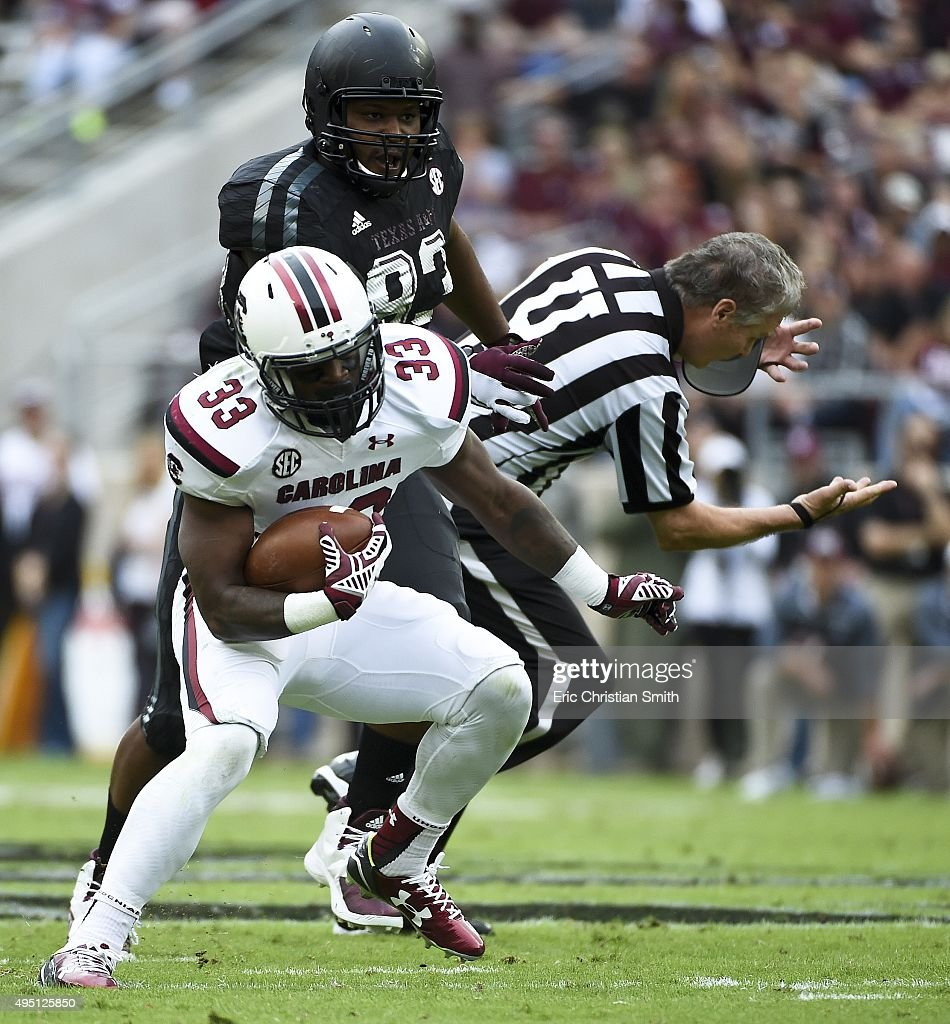 David Williams of the South Carolina Gamecocks scampers past Alonzo Williams of the Texas AM Aggies knocking down a referee in the first quarter of a...