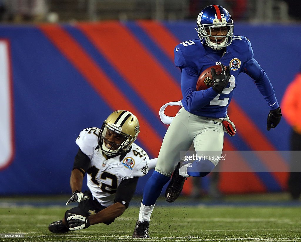 David Wilson #22 of the New York Giants carries the ball past Isa Abdul-Quddus #42 of the New Orleans Saints to score his third touchdown of the game on December 9, 2012 at MetLife Stadium in East Rutherford, New Jersey.