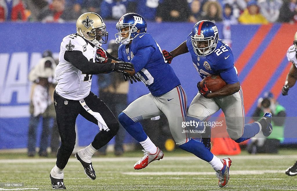 David Wilson #22 of the New York Giants runs the ball as teammate Victor Cruz #80 blocks Roman Harper #41 of the New Orleans Saints at MetLife Stadium on December 9, 2012 in East Rutherford, New Jersey. The Giants defeated the Saints 52-27.