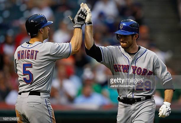 David Wright of the New York Mets congratulates teammate Ike Davis after he hit a two run home run against the Cleveland Indians during the game on...