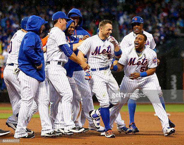 David Wright of the New York Mets is congratulated by Yoenis Cespedes and the rest of his teammates after Wright hit a walk off single to win the...