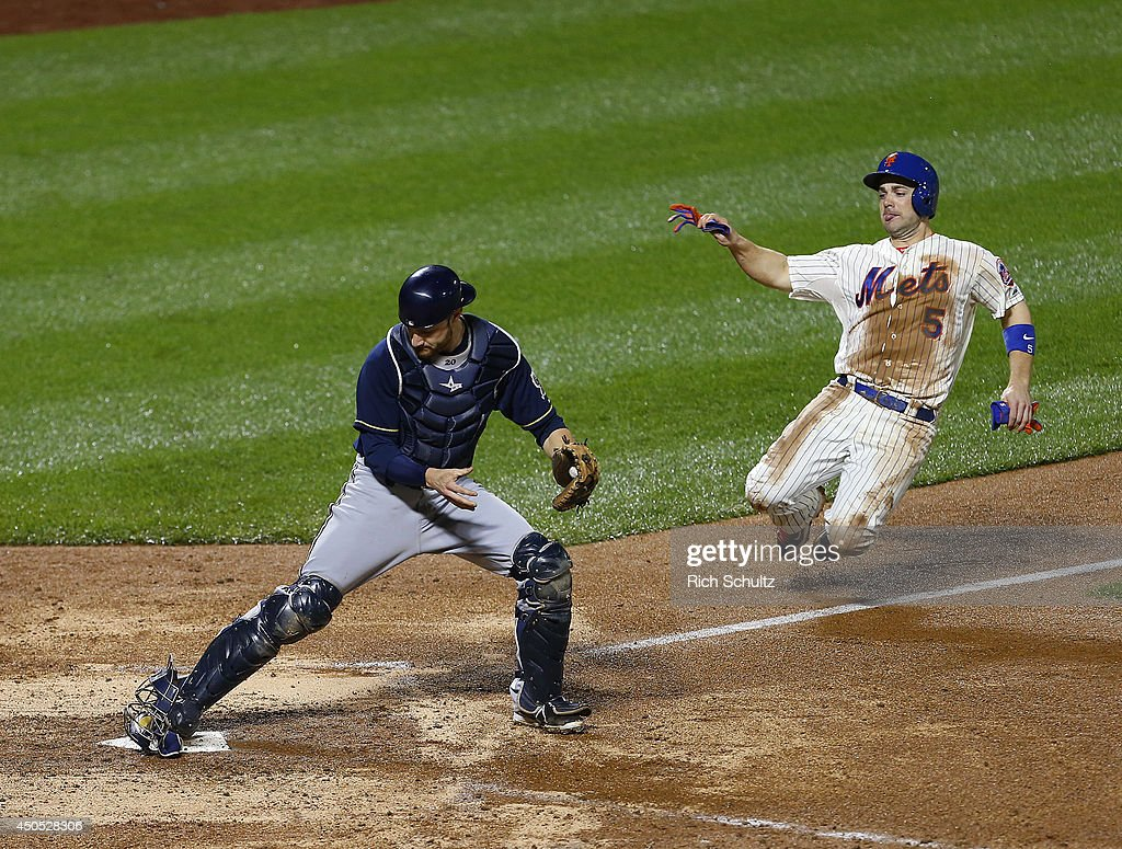David Wright #5 of the New York Mets is forced out at home plate by catcher Jonathan Lucroy #20 of the Milwaukee Brewers during the 11th inning on June 12, 2014 at Citi Field in the Flushing neighborhood of the Queens borough of New York City.