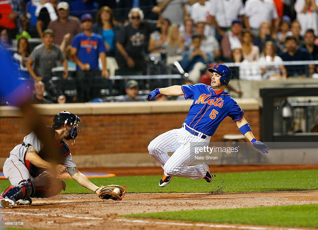 David Wright #5 of the New York Mets scores as he slides in to home on an RBI triple by Michael Cuddyer #23 in the fifth inning against the catcher Blake Swihart #23 of the Boston Red Sox on August 28, 2015 at Citi Field in the Flushing neighborhood of the Queens borough of New York City.