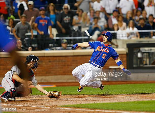 David Wright of the New York Mets scores as he slides in to home on an RBI triple by Michael Cuddyer in the fifth inning against the catcher Blake...