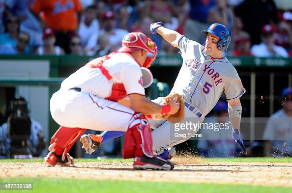 David Wright of the New York Mets scores in the seventh inning ahead of the tag of Wilson Ramos of the Washington Nationals at Nationals Park on...