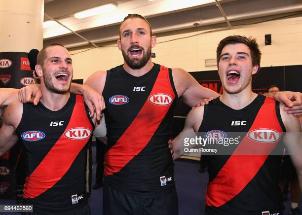 David Zaharakis Cale Hooker and Zach Merrett of the Bombers sing the song in the rooms after winning the round 12 AFL match between the Essendon...