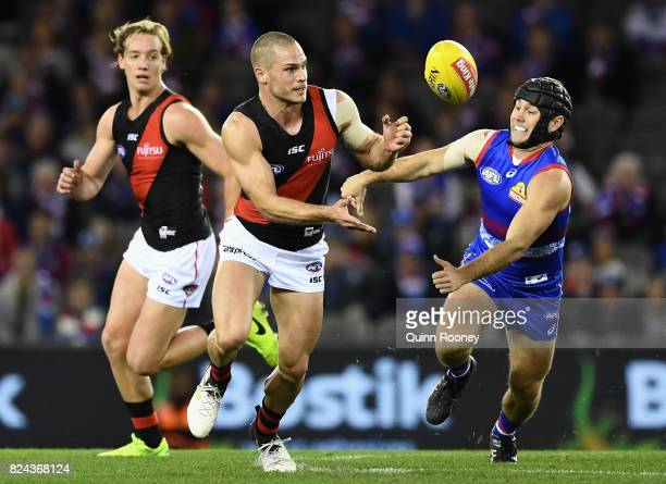 David Zaharakis of the Bombers handballs whilst being tackled by Caleb Daniel of the Bulldogs during the round 19 AFL match between the Western...
