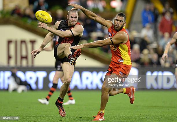 David Zaharakis of the Bombers has his kick charged down by Harley Bennell of the Suns during the round 21 AFL match between the Gold Coast Suns and...