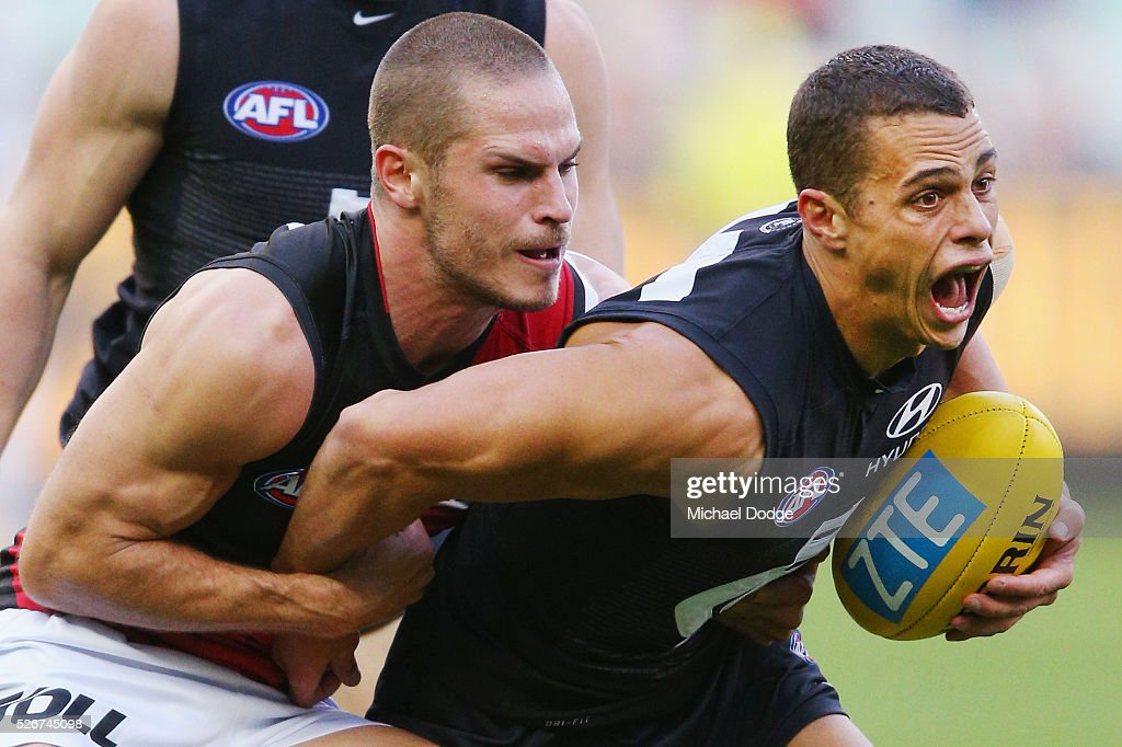 David Zaharakis of the Bombers tackles Ed Curnow of the Blues during the round six AFL match between the Carlton Blues and the Essendon Bombers at Melbourne Cricket Ground on May 1, 2016 in Melbourne, Australia.