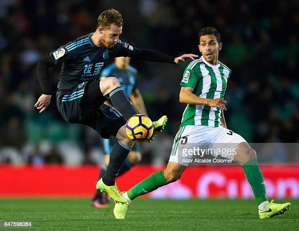 David Zurutuza of Real Sociedad being followed by Petros Matheus dos Santos of Real Betis Balompie during La Liga match between Real Betis Balompie...