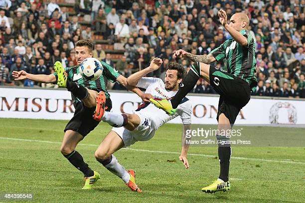 Davide Astori of Cagliari Calcio competes the ball with Simione Zaza of US Sassuolo Calcio and Gaetano Masucci of US Sassuolo Calcio during the Serie...
