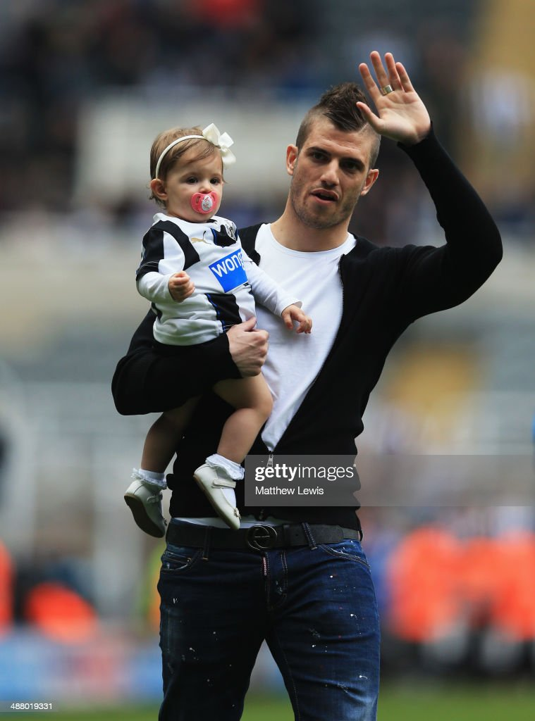 Davide Santon of Newcastle United carries daughter Sienna as he waves to fans after the Barclays Premier League match between Newcastle United and...