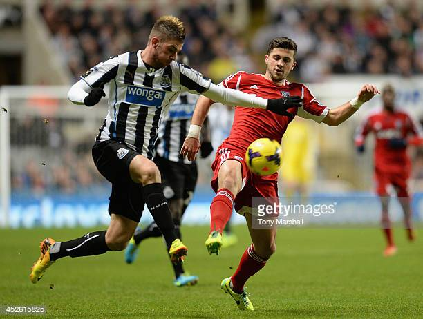 Davide Santon of Newcastle United competes with Shane Long of West Bromwich Albion during the Barclays Premier League match between Newcastle United...