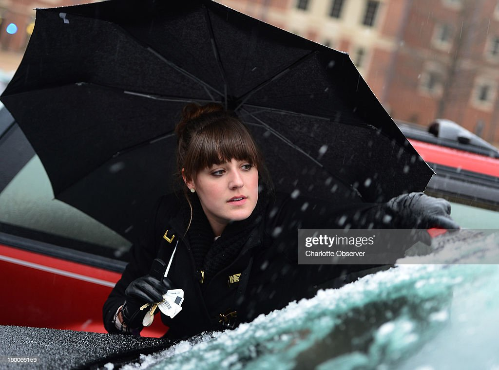Davidson College junior Elizabeth Anderson cleans ice from the windshield of her vehicle as sleet continues to fall in Davidson, North Carolina, as sleet falls, Friday, January 25, 2013.