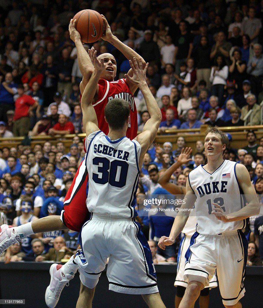 Davidson guard Stephen Curry (30) attempts to shoot over Duke guard Jon Scheyer (30), as forward Kyle Singler (12) looks on, during the second half at Cameron Indoor Stadium in Durham, North Carolina, Wednesday, January 7, 2009. Duke defeated Davidson, 79-67.