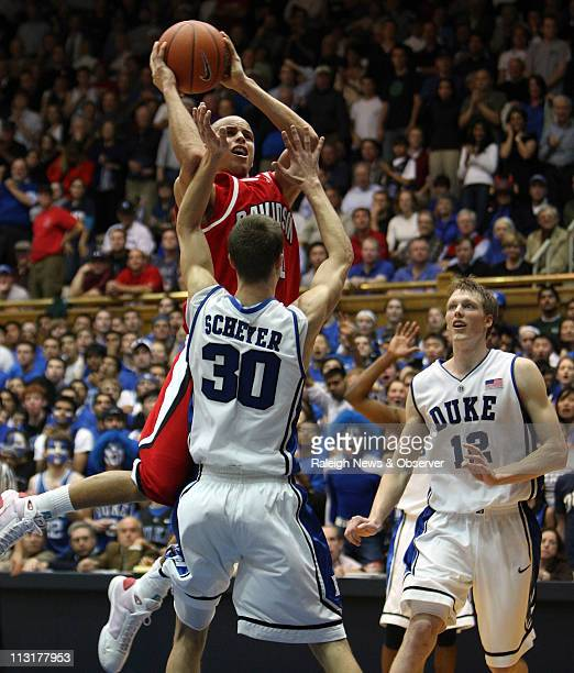 Davidson guard Stephen Curry attempts to shoot over Duke guard Jon Scheyer as forward Kyle Singler looks on during the second half at Cameron Indoor...