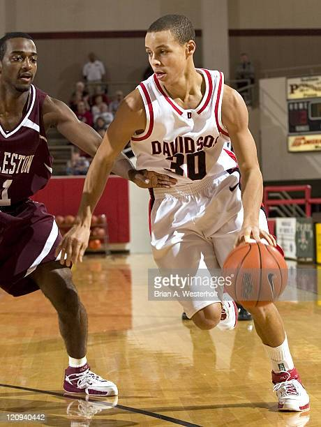 Davidson guard Stephen Curry drives to the basket around College of Charleston guard Marcus Hammond during first half action at Belk Arena in...
