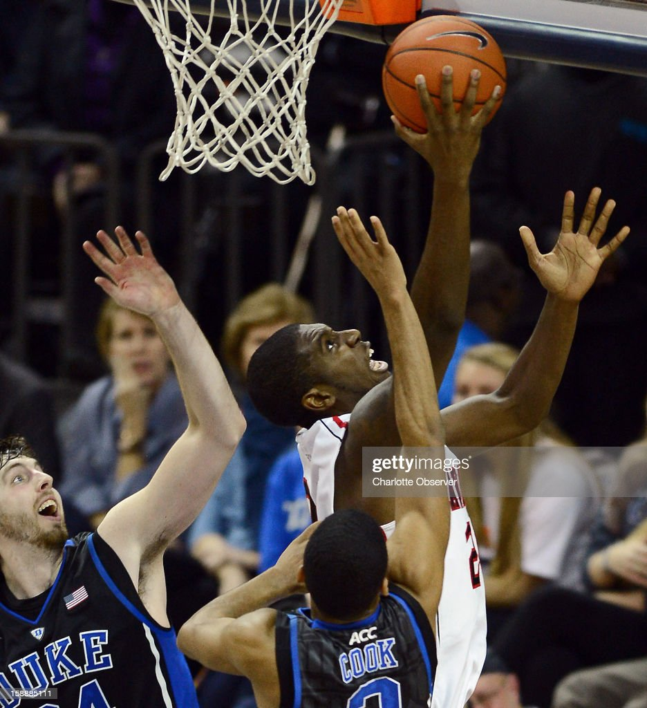 Davidson's De'Mon Brooks, right, fights his way to the basket for two points as Duke's Ryan Kelly, left, and Quinn Cook apply defensive pressure during first-half action at Time Warner Arena in Charlotte, North Carolina, on Wednesday January 2, 2013.