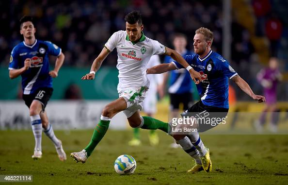 Davie Selke of Werder Bremen is challenged by Felix Burmeister of Arminia Bielefeld during the round of 16 DFB Cup match between Arminia Bielefeld...