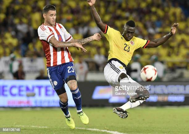 Davinson Sanchez of Colombia struggles for the ball with Antonio Sanabria of Paraguay during a match between Colombia and Paraguay as part of FIFA...