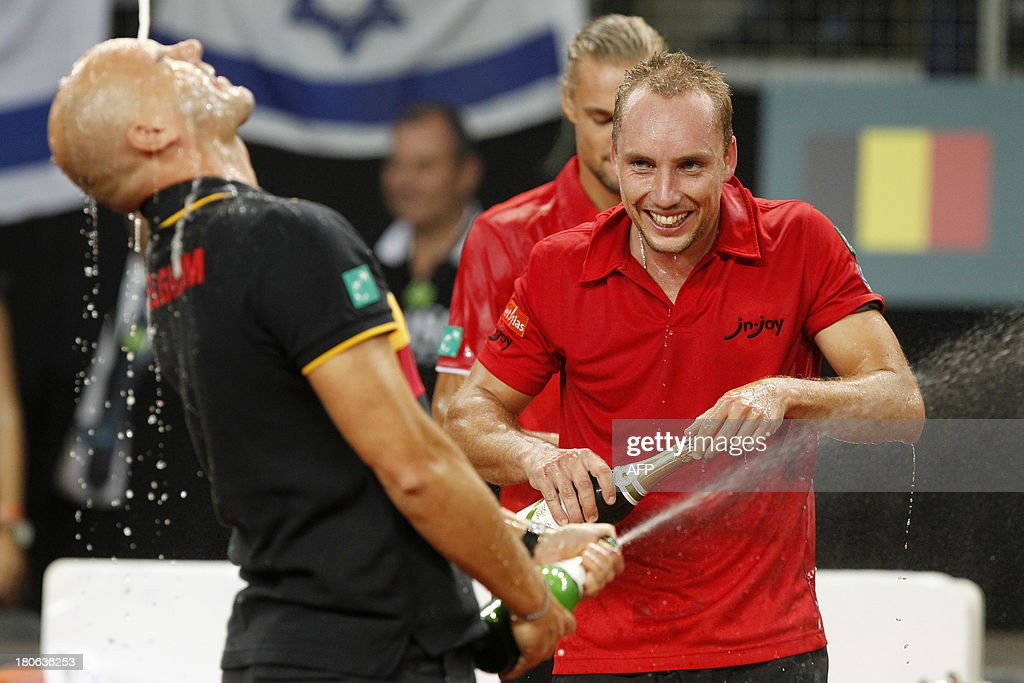 Davis Cup captain Johan Van Herck (L) and Belgian Steve Darcis celebrate with champagne after the latter defeated Israeli Amir Weintraub on September 15, 2013 in a Davis Cup World Group play-off tennis match in Antwerp.
