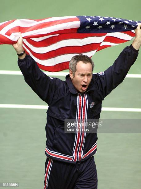 S Davis Cup captain John McEnroe carries the US flag after Pete Sampras defeated Slava Dosedel of the Czech Republic during the Davis Cup...