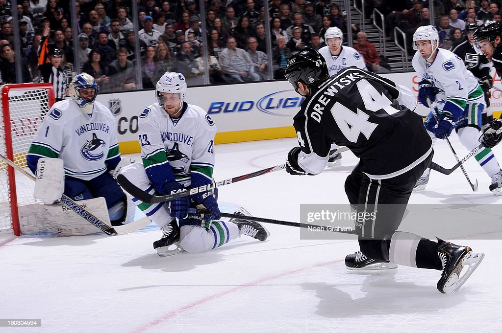 Davis Drewiske #44 of the Los Angeles Kings shoots the puck against Alexander Edler #23 of the Vancouver Canucks at Staples Center on January 28, 2013 in Los Angeles, California.