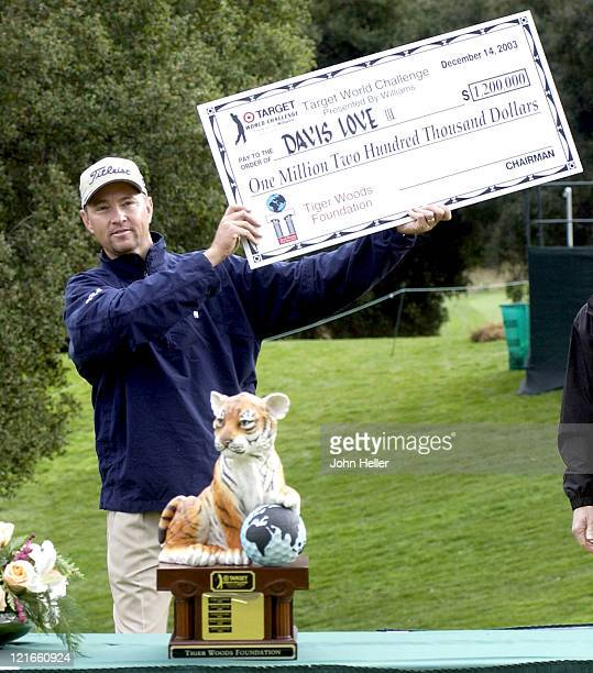 Davis Love III holds up his paycheck of $1000 for winning the 2003 Target World Challenge
