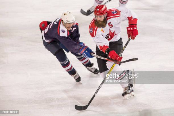 Davis Vandane of Team Canada and Austin Smith of Team USA contest the puck during the Melbourne Game of the Ice Hockey Classic on June 24 2017 held...