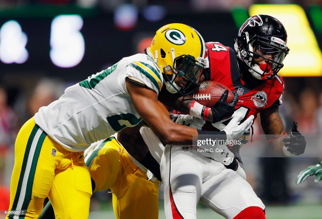 Davon House #31 (obscured) and Kevin King #20 of the Green Bay Packers attempt to tackle Justin Hardy #14 of the Atlanta Falcons during the first half at Mercedes-Benz Stadium on September 17, 2017 in Atlanta, Georgia.