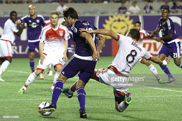 Davy Arnaud of DC United tackles Kaka of Orlando City SC from behind during a MLS soccer match between DC United and the Orlando City SC at the...