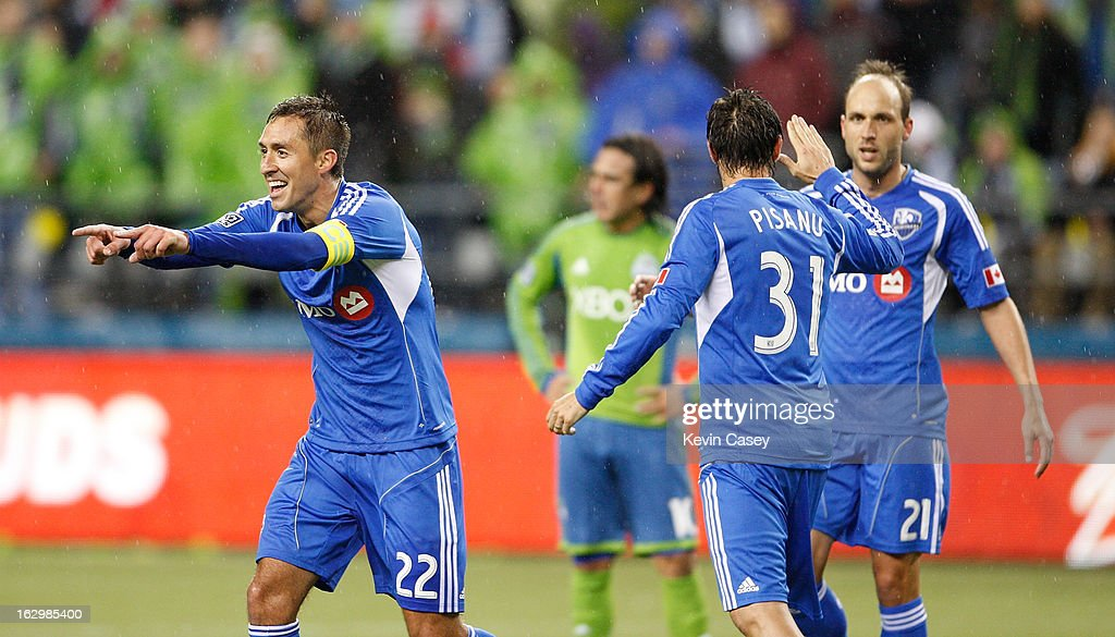 Davy Arnaud #22 of Montreal Impact celebrates his goal with teammates Andrea Pisanu #31 and Justin Mapp #21 in the first half against Seattle Sounders at CenturyLink Field on March 2, 2013 in Seattle, Washington.