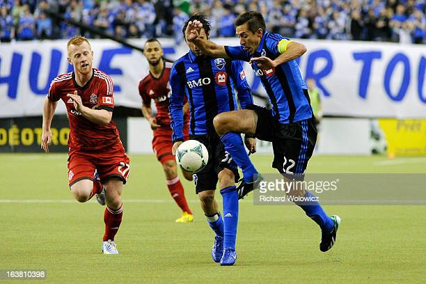 Davy Arnaud of Montreal Impact moves the ball past Richard Eckersley of Toronto FC during the MLS game at the Olympic Stadium on March 16 2013 in...