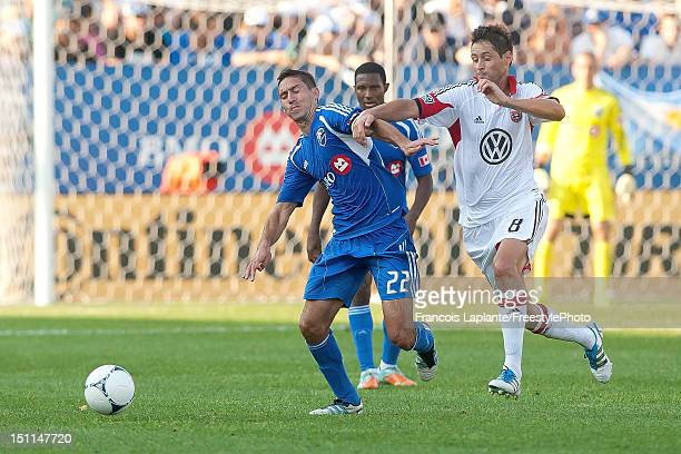 Davy Arnaud of the Montreal Impact battles for a loose ball against Branko Boskovic of the DC United during the MLS match at Saputo Stadium on August...