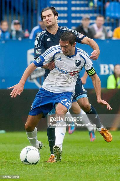 Davy Arnaud of the Montreal Impact controls the ball against Michael Harrington of the Sporting KC during the MLS match at Saputo Stadium on...