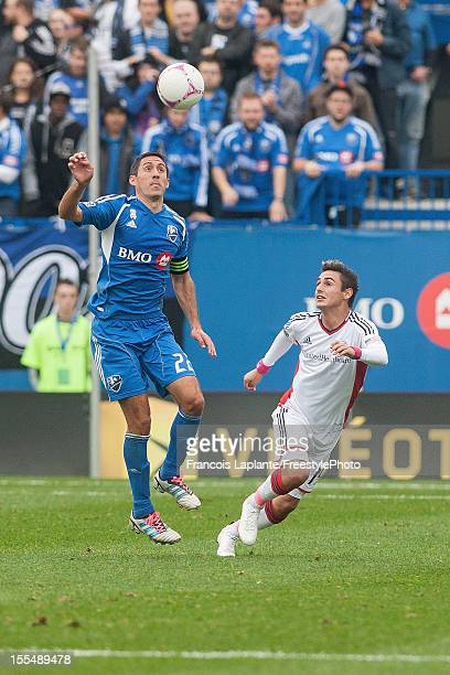 Davy Arnaud of the Montreal Impact heads the ball against Diego Fagundez of the New England Revolution during the MLS match at Saputo Stadium on...