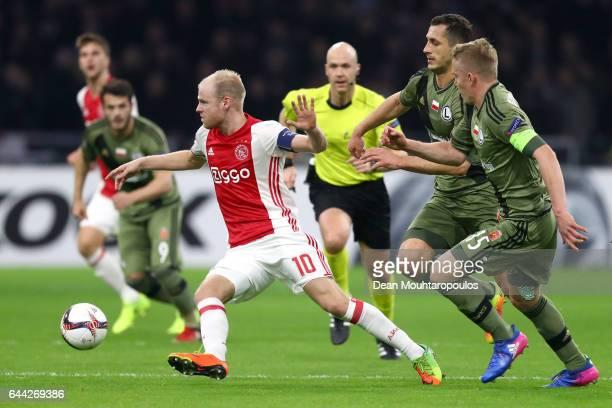 Davy Klaassen of Ajax evades Tomasz Jodlowiec and Michal Kopczynski of Legia Warszawa during the UEFA Europa League Round of 32 second leg match...