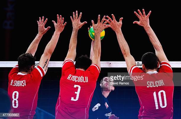 Dawid Konarski of Poland is blocked by Burutay Subasi Ahmet Tocoglu and Selcuk Keskin of Turkeyduring the Men's Volleyball Group A match between...