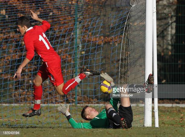 Dawid Kownacki of Poland scores his team's first goal against goalkeeper Patrick Bade of Germany during the U15 International Friendly match between...